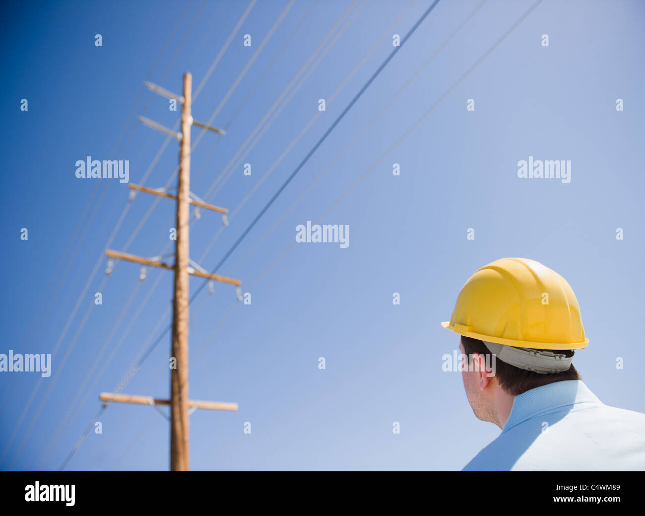 USA, California, Palm Springs, Coachella Valley, San Gorgonio Pass, Man in hard hat looking at telephone pole - Stock Image