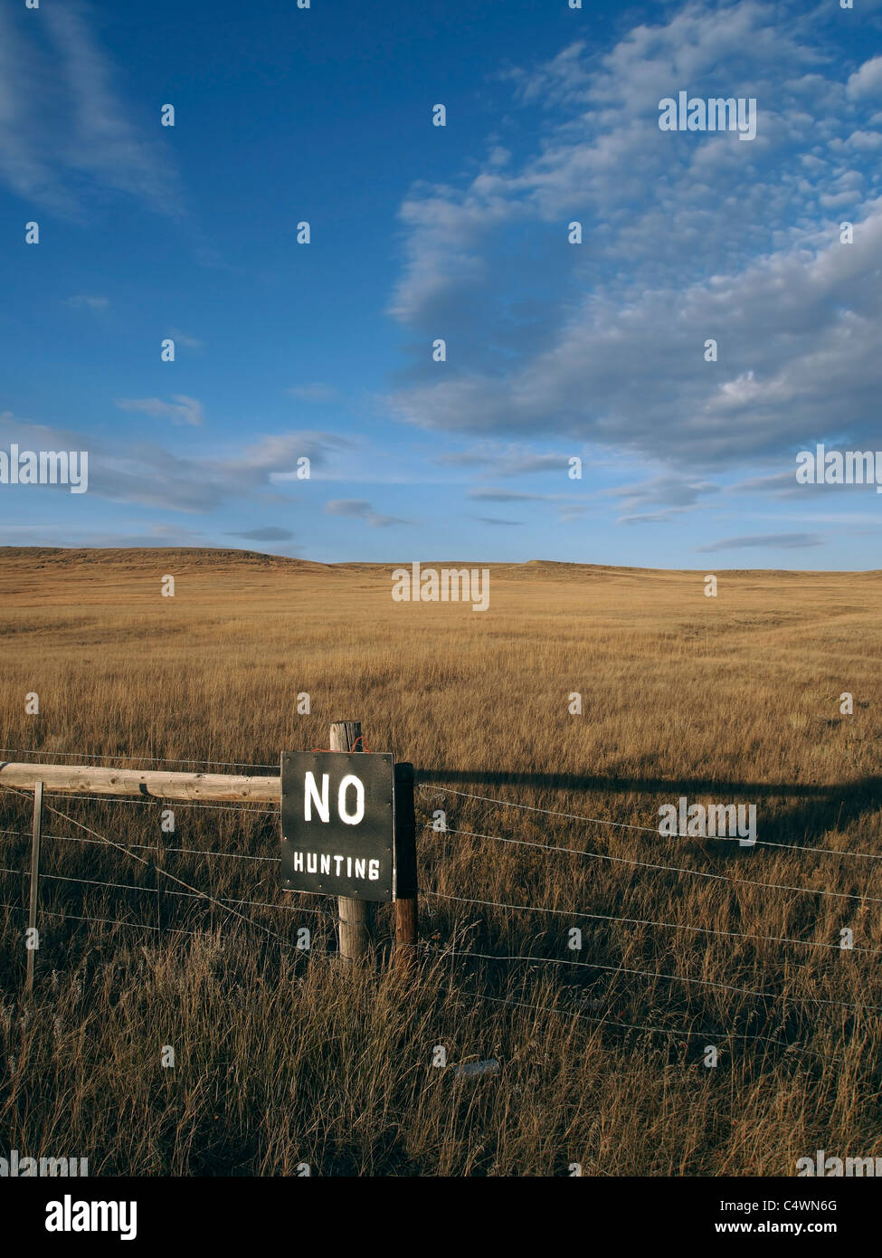 a painted sign warns against hunting the open prairie stock photo