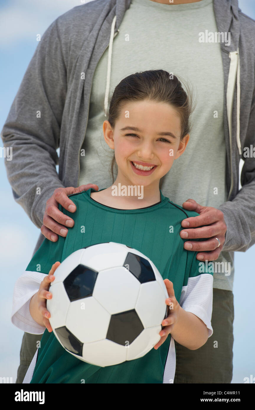 USA,New Jersey,Jersey City,girl (8-9) holding soccer ball,with father behind - Stock Image