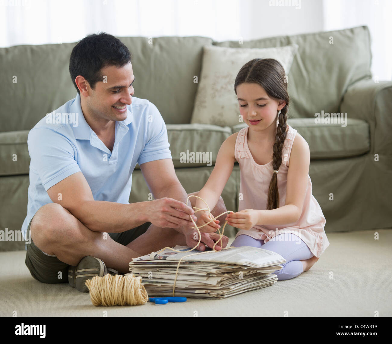 USA, New Jersey, Jersey City, father and daughter (8-9) wrapping up wastepaper bundle - Stock Image