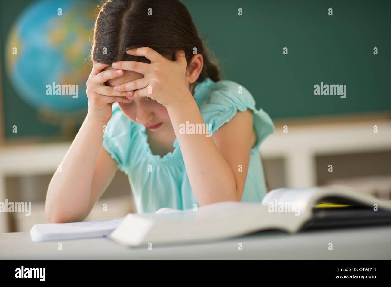USA,New Jersey,Jersey City,schoolgirl (8-9) reading book - Stock Image