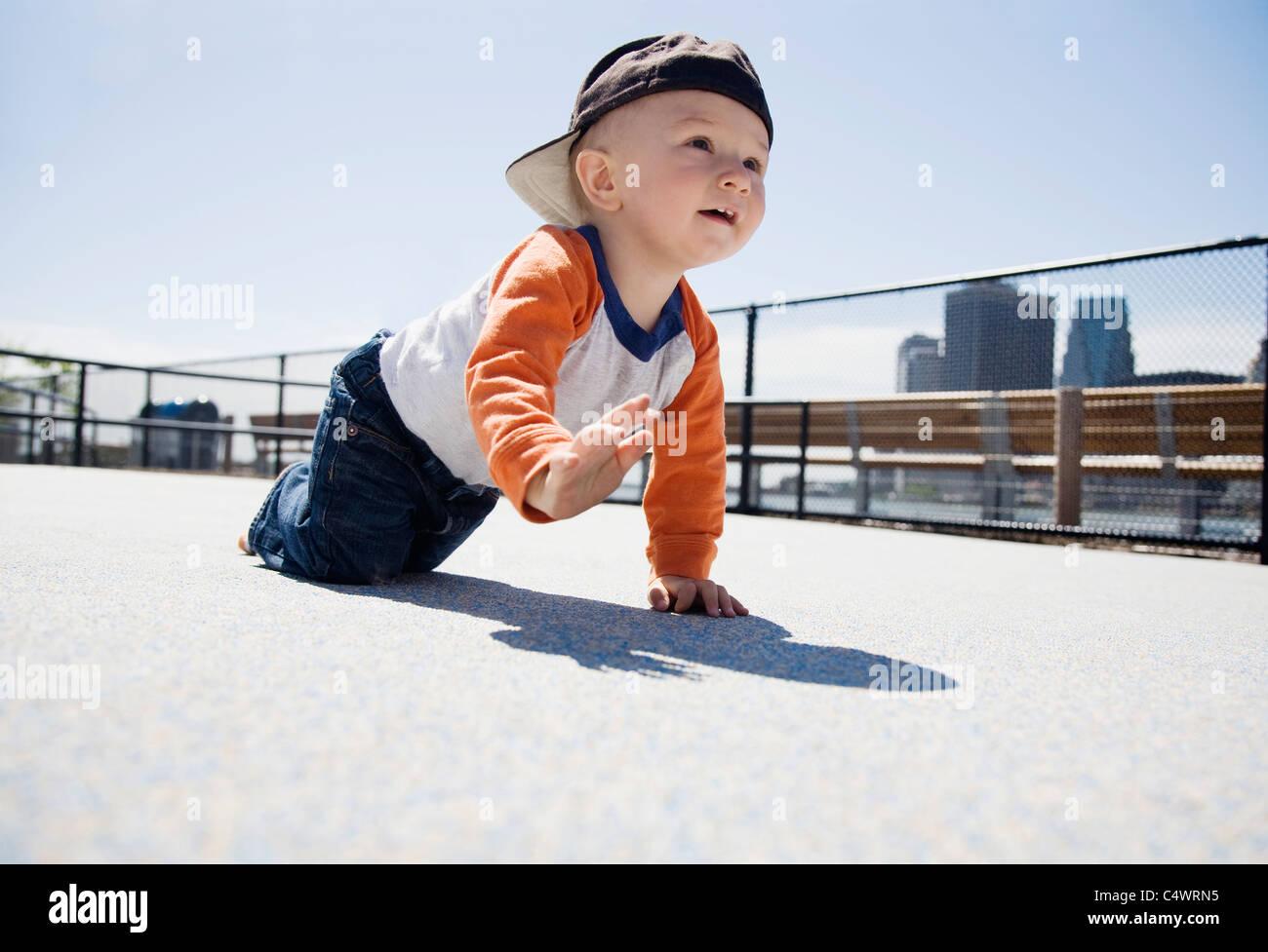 USA,New York City,Brooklyn,baby boy (0-1 years) crawling on sidewalk - Stock Image