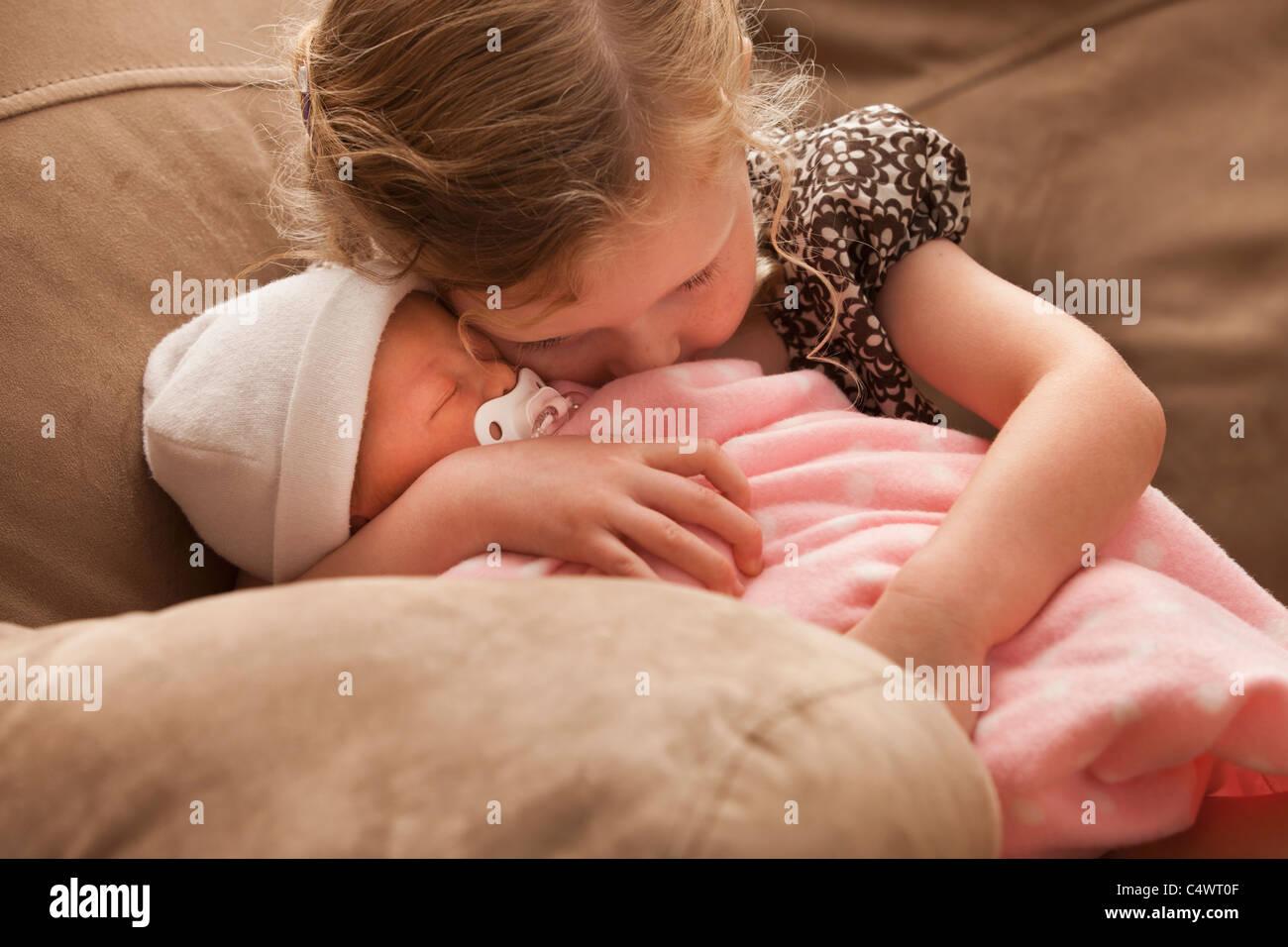 USA,Utah,Lehi,Girl (2-3) embracing baby sister on sofa - Stock Image