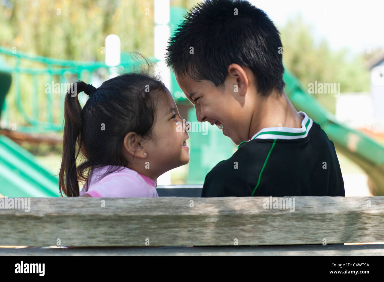 USA, California, Brother and sister (4-13) face to face at playground - Stock Image