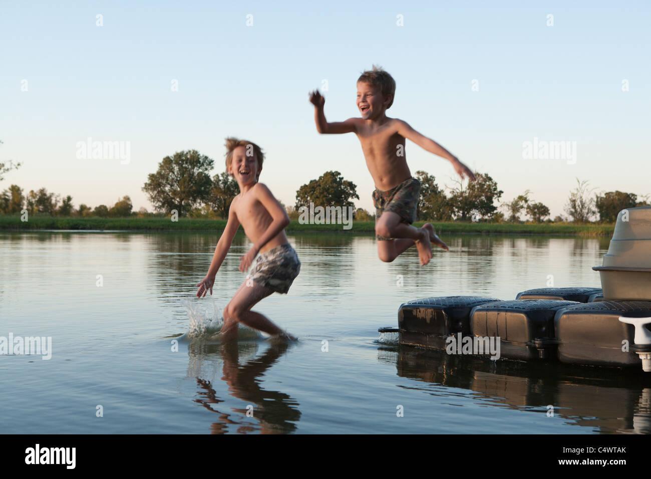 USA,Texas,Texarkana,Two boys (8-9) jumping into lake - Stock Image