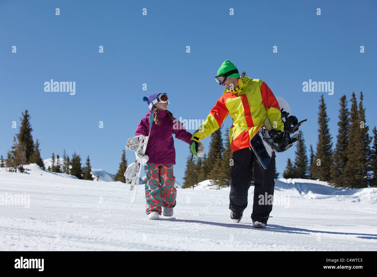 USA, Colorado, Telluride, Father and daughter (10-11) walking with snowboards in winter scenery - Stock Image