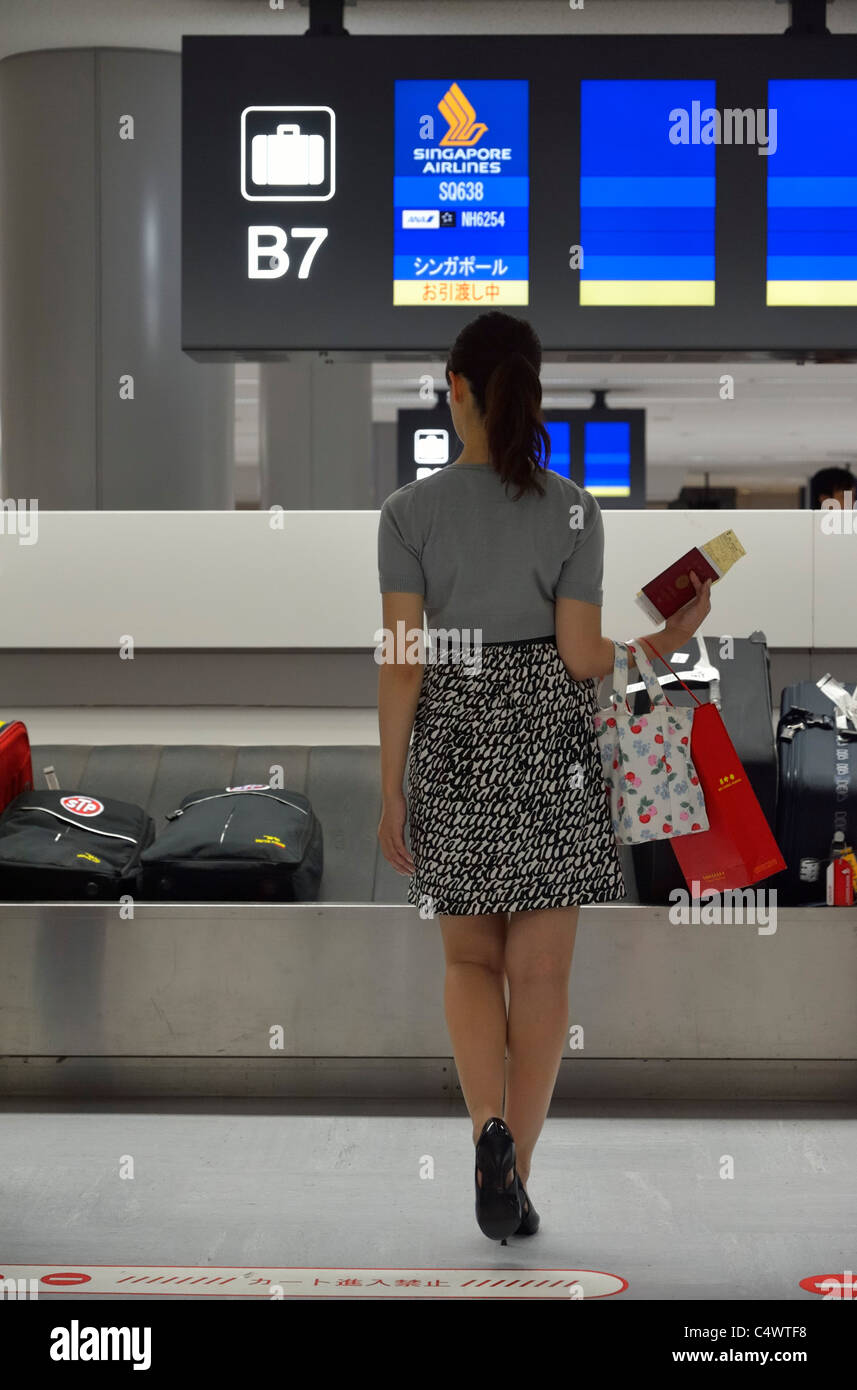 A young woman is waiting for her baggage delivery upon arrival at Tokyo Narita, Japan JP - Stock Image