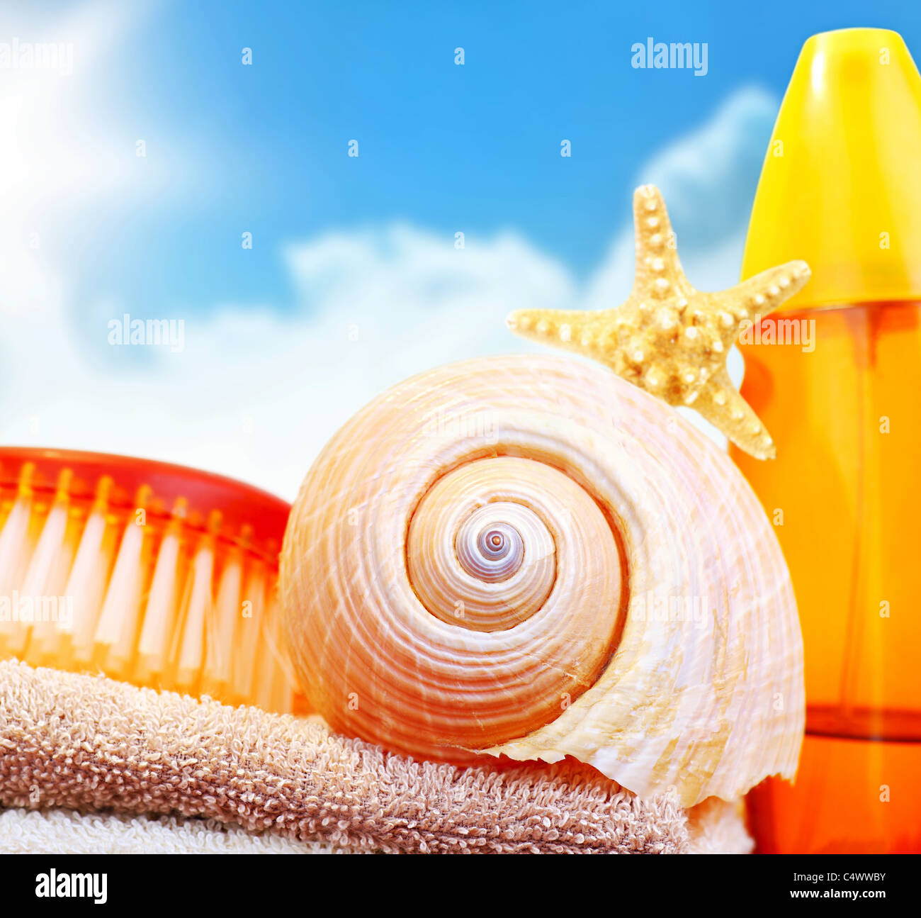 Beach items over blue sky conceptual image of summertime vacation & holidays - Stock Image