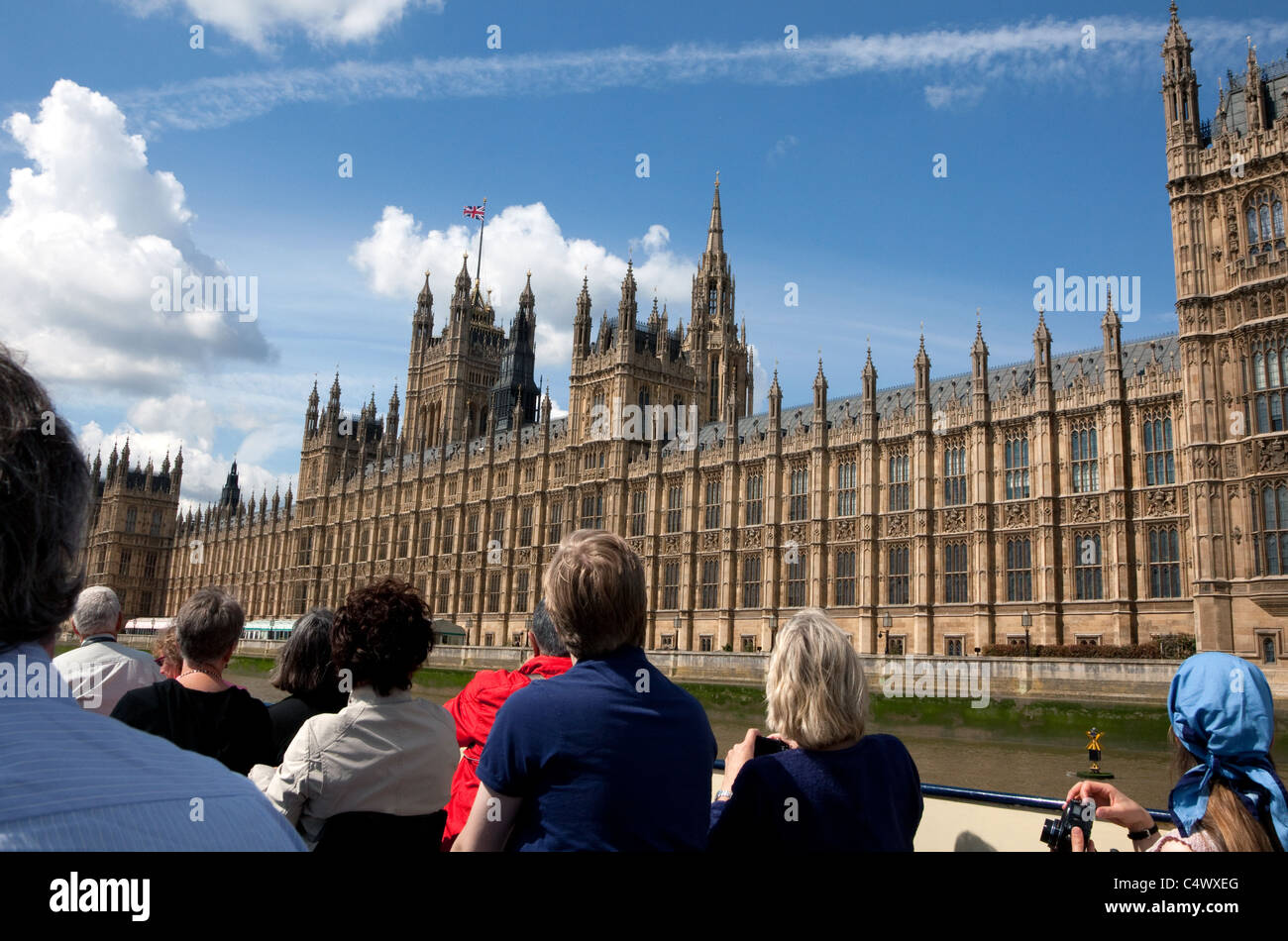 Sightseers on Thames river cruise pass Houses of Parliament, Westminster, London - Stock Image
