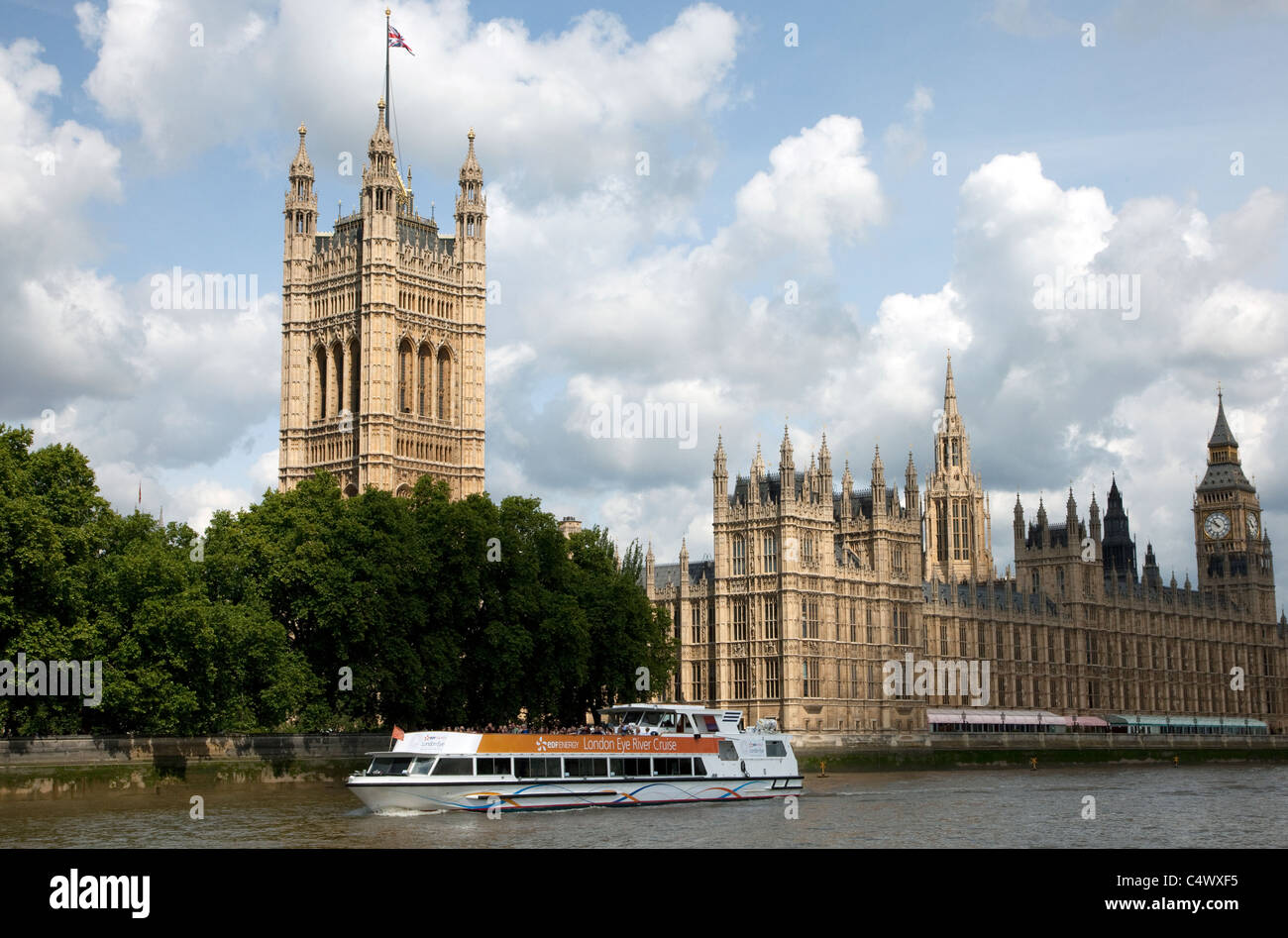 River Thames cruise boat passes Houses of Parliament, London - Stock Image