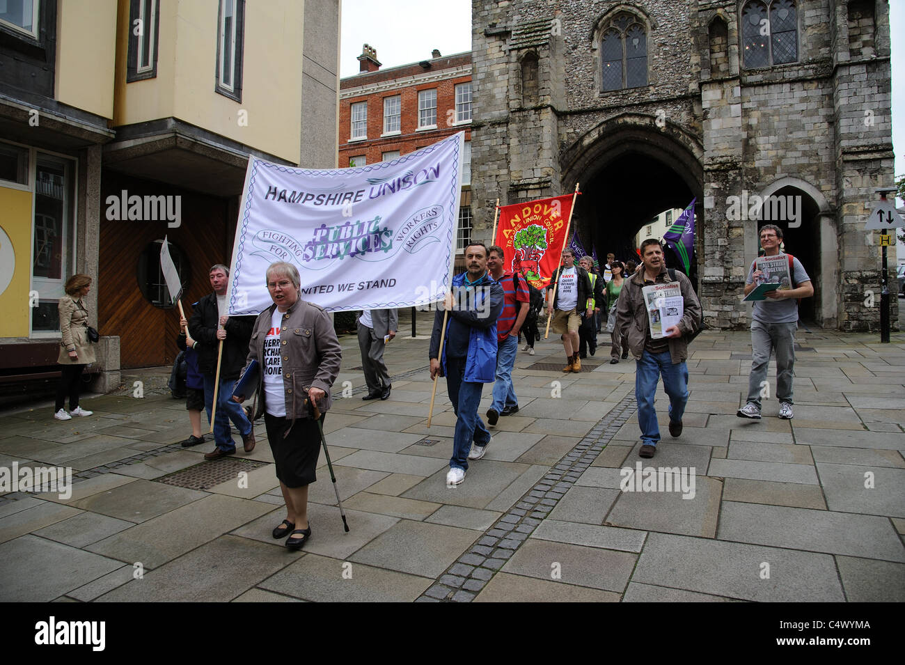 Trade Unionists protesting against public service cuts enter the historic city of Winchester via the Westgate - Stock Image