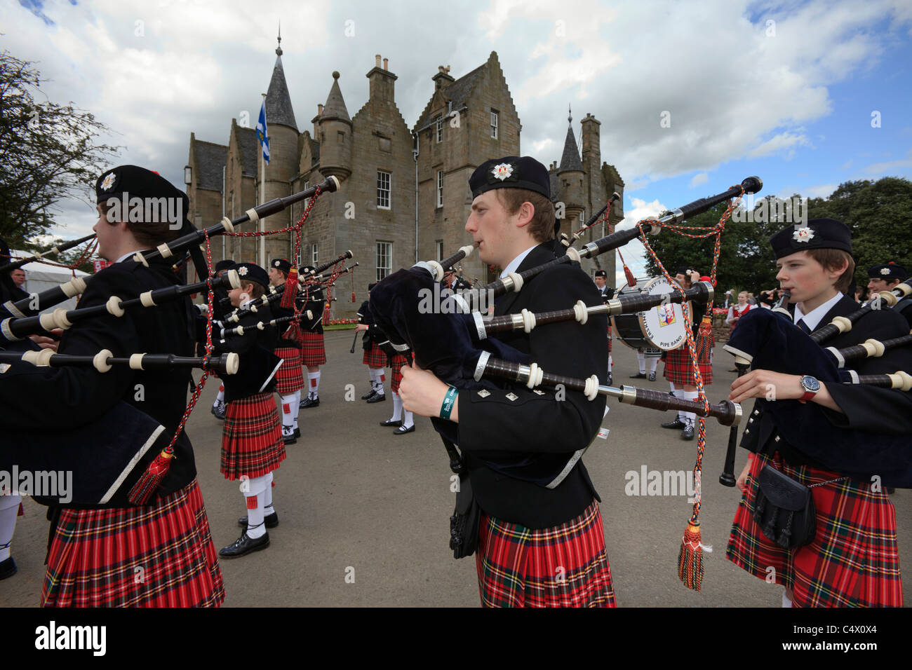Erskine Stewart's Melville School's pipe band march past the RHASS headquarters building at the Royal Highland - Stock Image