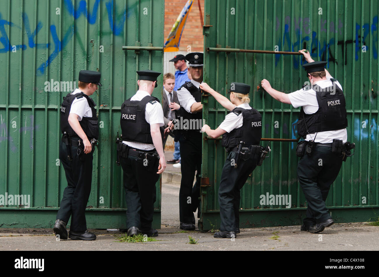 Police officers open the gates at the Peace Wall separating Protestant Workman Avenue from the Catholic Springfield - Stock Image