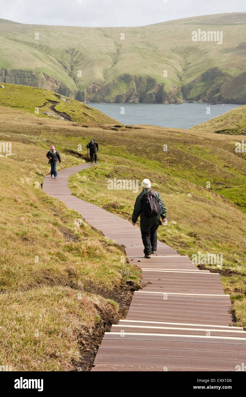 Walkers on path boardwalk made from recycled plastic on Hermaness National Nature Reserve, Unst, Shetland Islands, - Stock Image