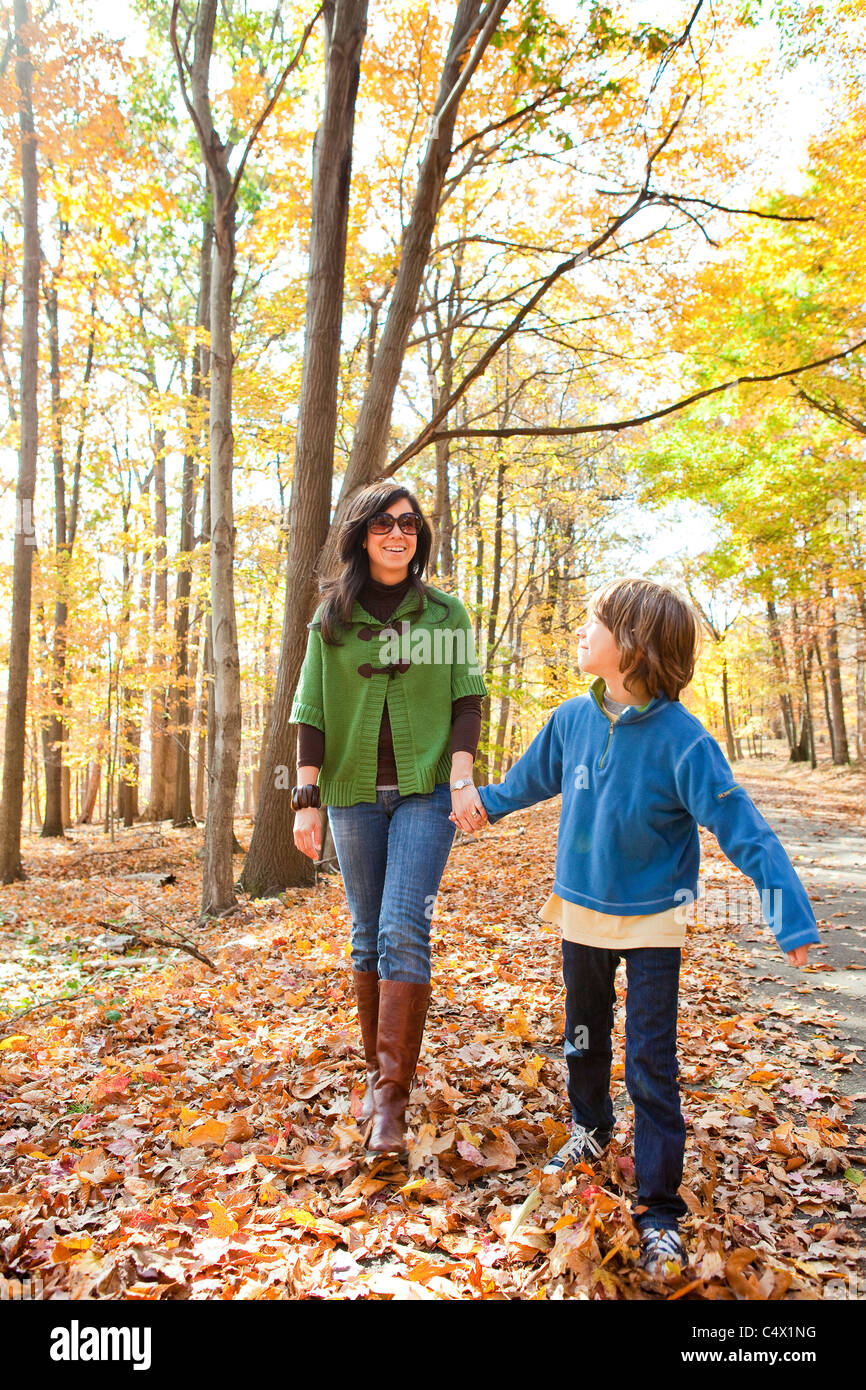 mother and son walking through woods - Stock Image