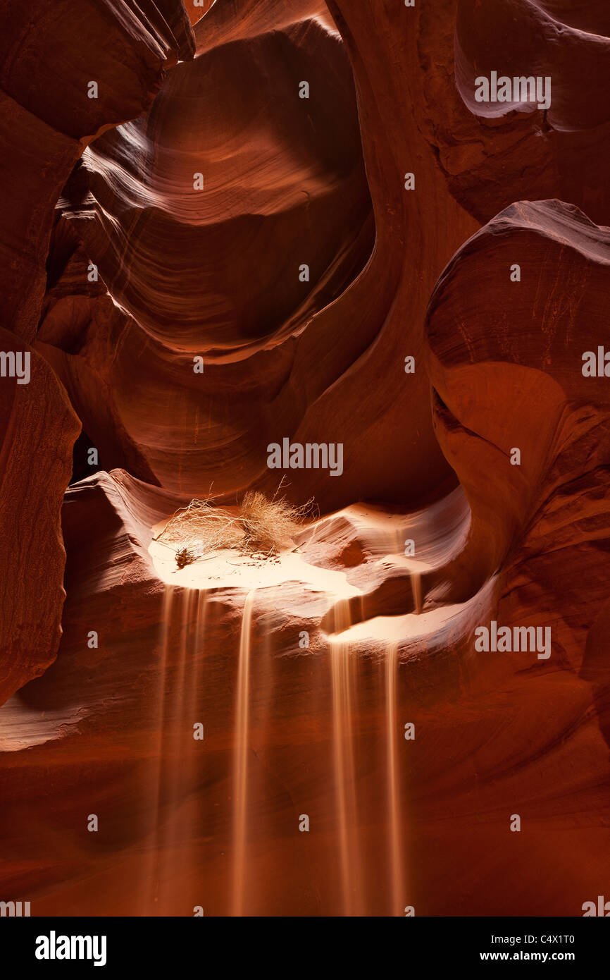 Sunlight illuminating sculpted curves and lines carved in red sandstone walls of Antelope Canyon by water erosion Stock Photo