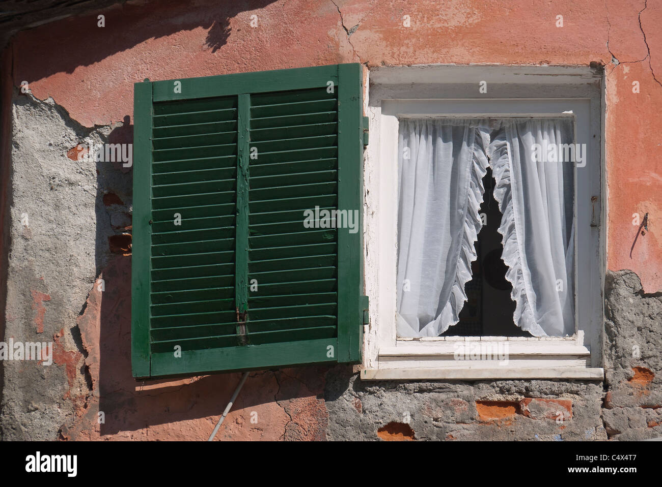 Older Window With Shear Curtains And A Green Shutter Salmon Colored Stucco Wall In Monterosso Italy