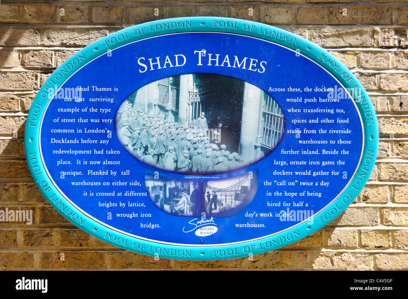 Historical data recorded on large blue wall plaque describing the type of warehousing street found at back of London - Stock Image