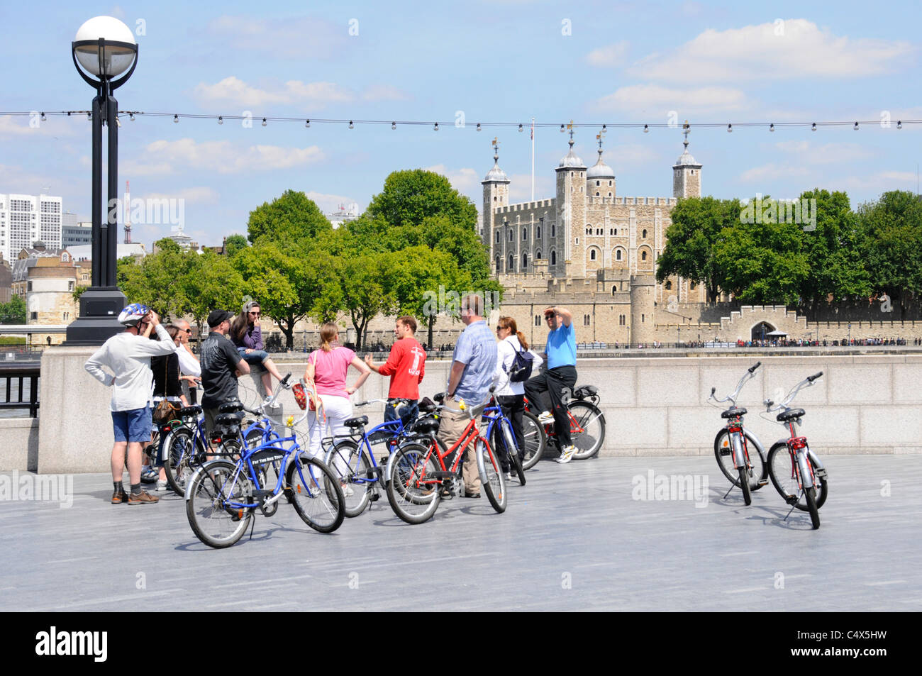 Group of tourists using hired bikes on escorted sightseeing trip listening to tour guide (in red) opposite the Tower Stock Photo