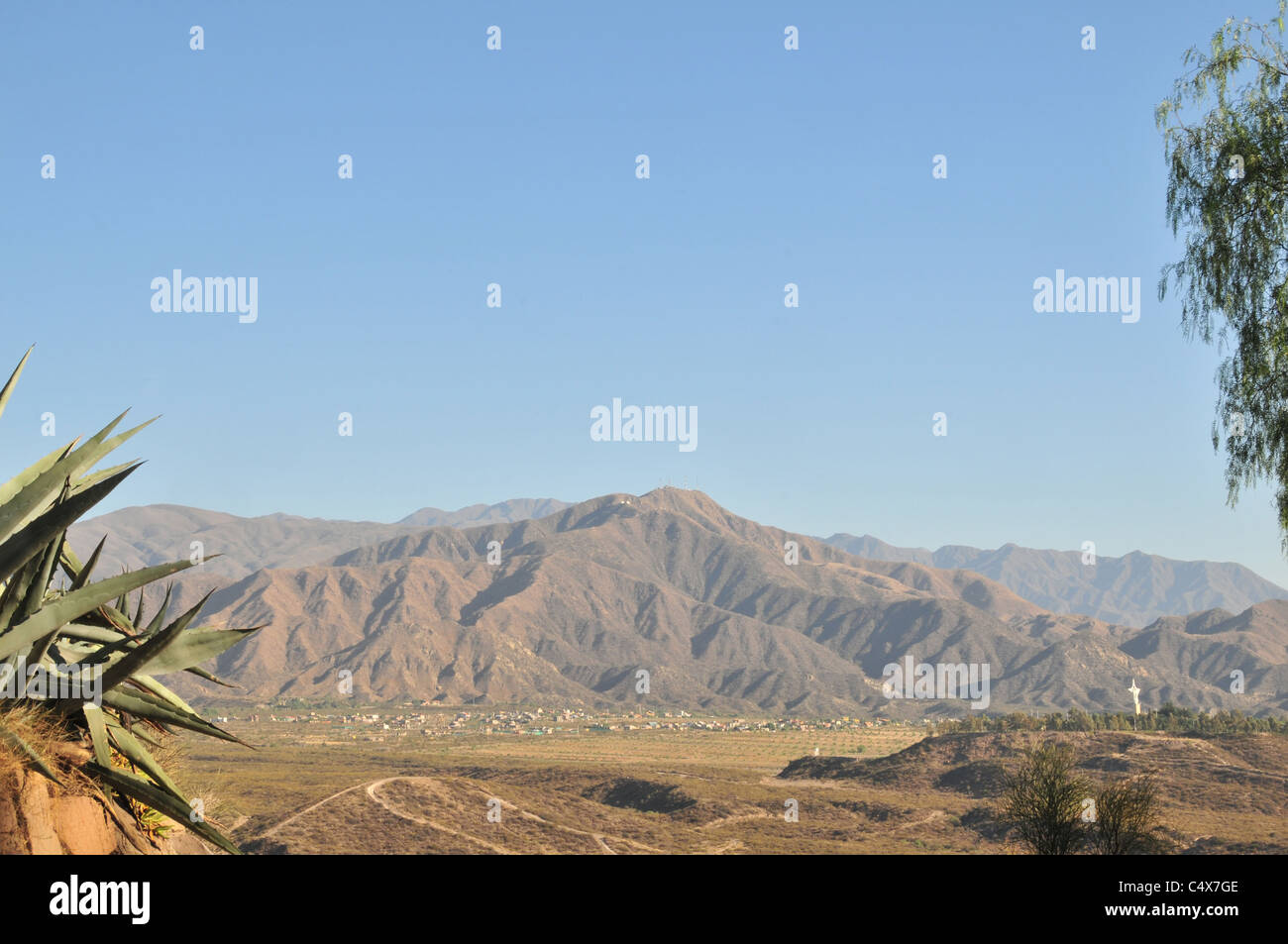 Blue sky cactus view of gullied Andean peaks, brown arid landscape and white cross, west of Cerro Gloria, Mendoza, - Stock Image