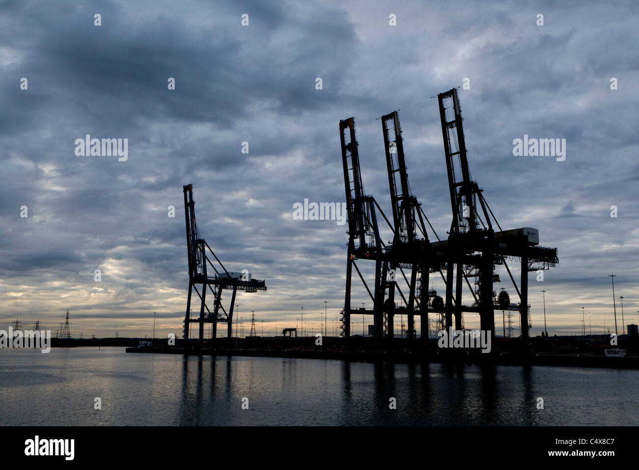Container cranes stand idle at sunset in Southampton docks. - Stock Image