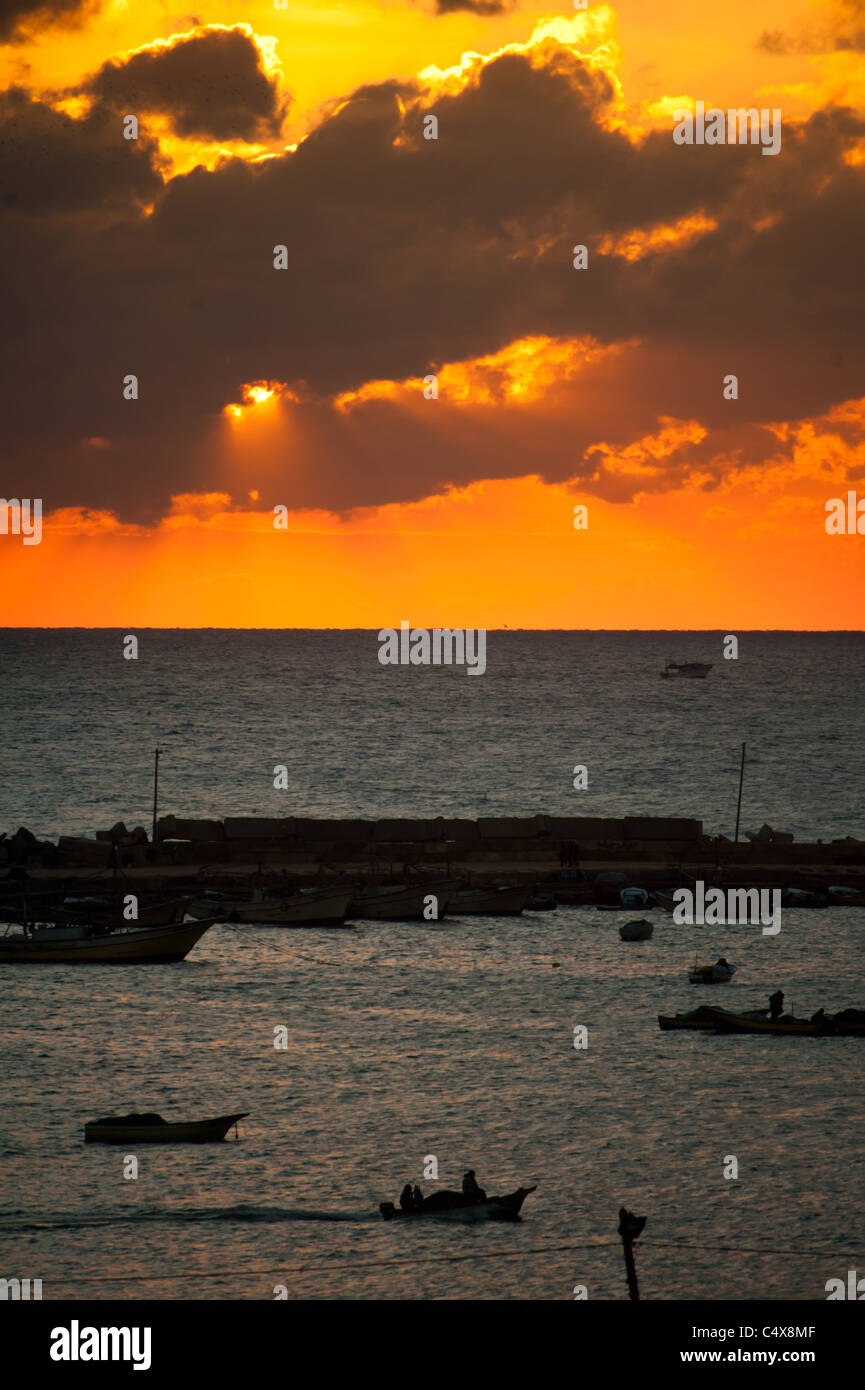 Dramatic clouds and sky at sunset over the harbor at Gaza City. - Stock Image