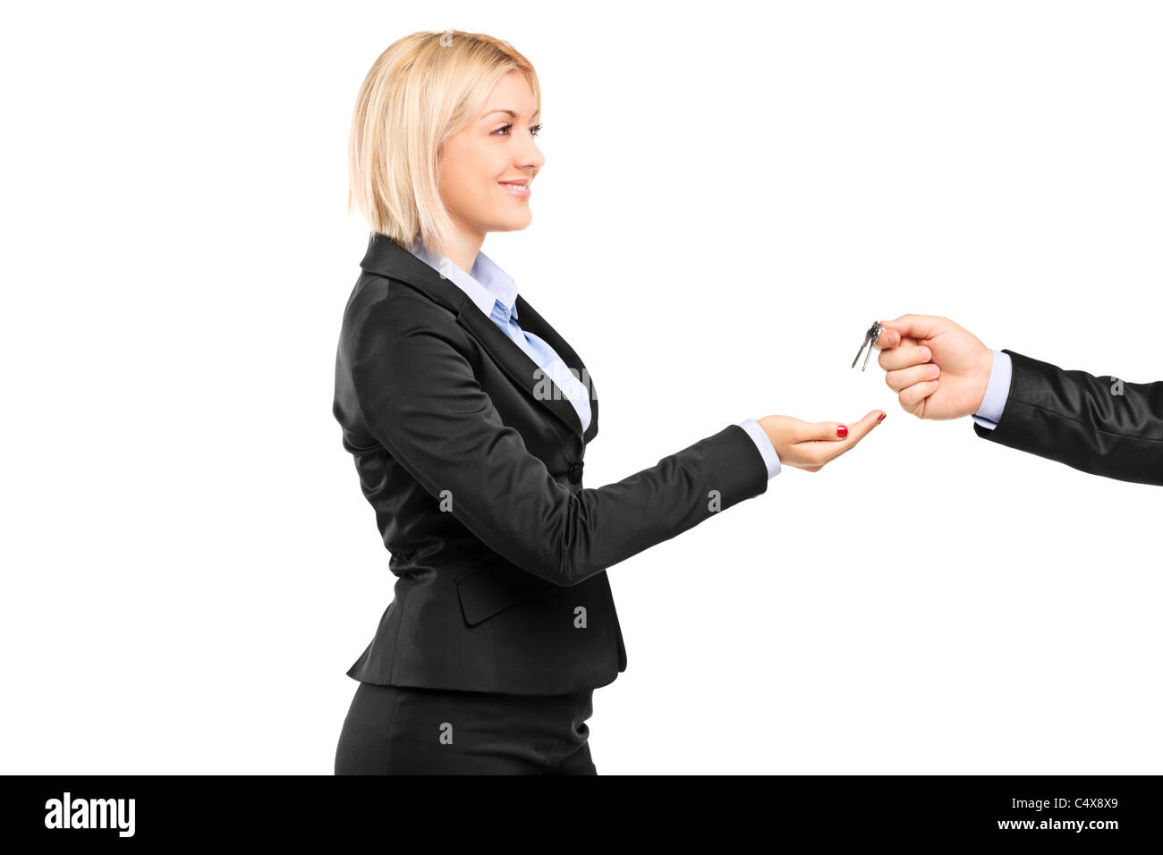 A blond businesswoman taking a key from a businessman - Stock Image