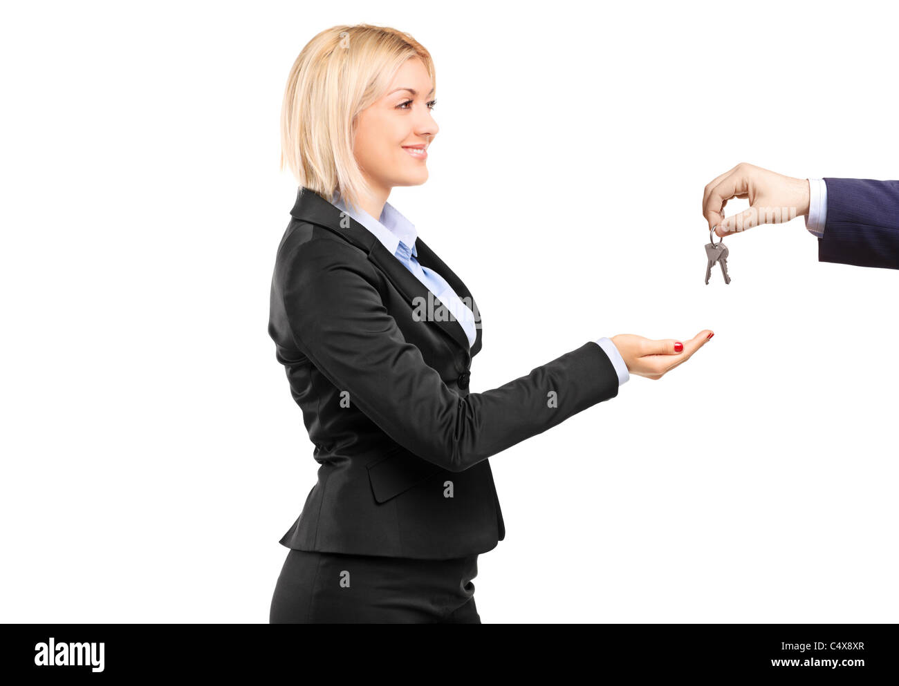 A blond businesswoman taking keys from a businessman - Stock Image