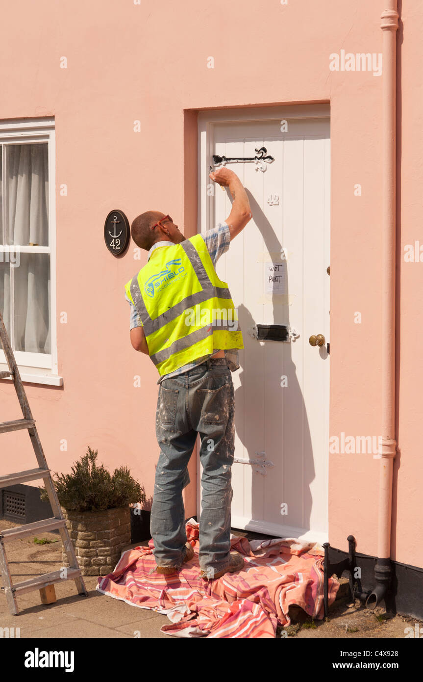A painter and decorator at work painting an exterior door in the Uk - Stock Image