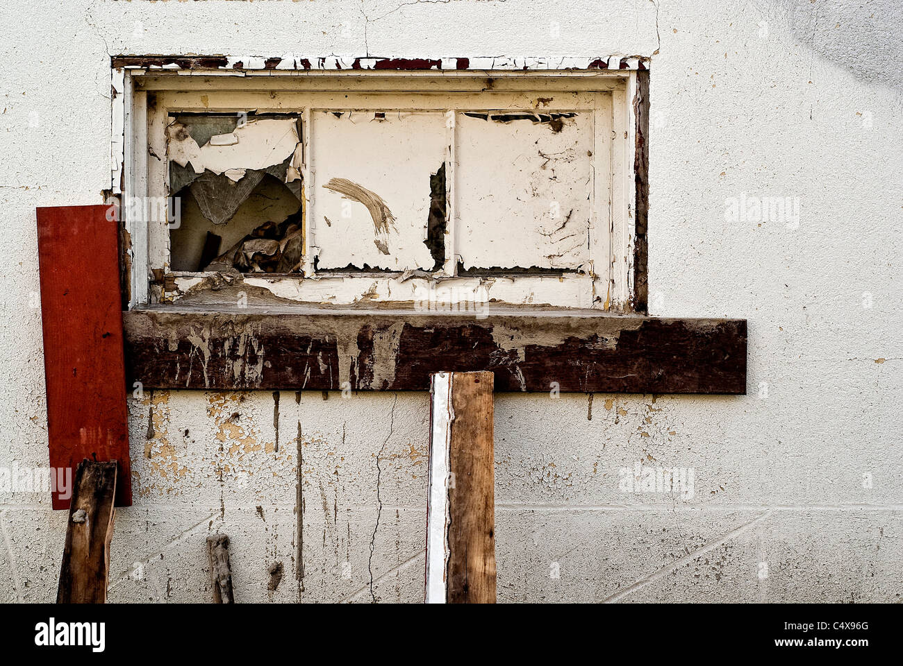 An old window on the white wall of a run-down building. - Stock Image
