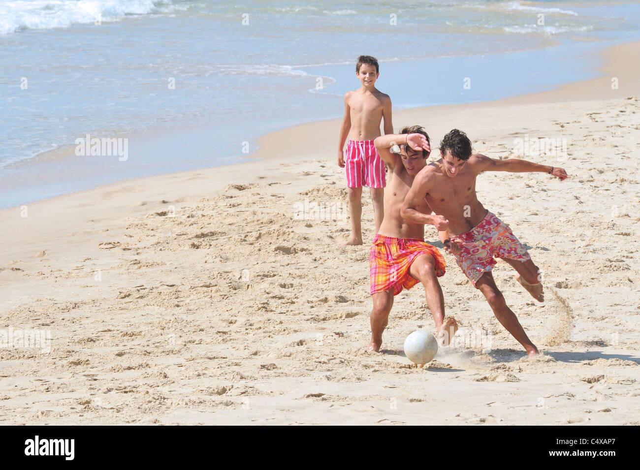 Israeli boys play football in the hot weather in Nitzanim beach, Israel. Stock Photo