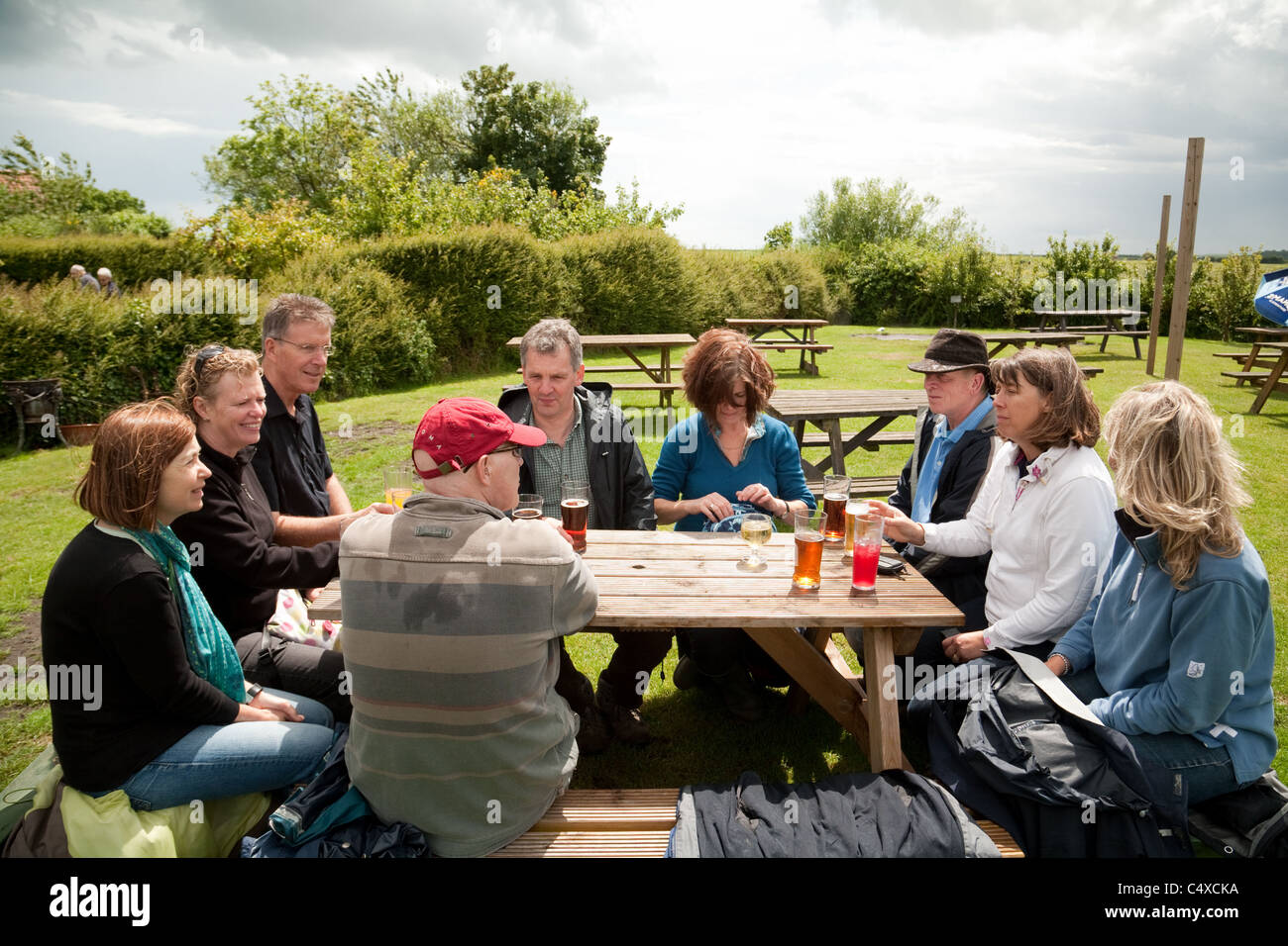 A group of people drinking in The Jolly Sailor pub beer garden, Orford, Suffolk UK - Stock Image