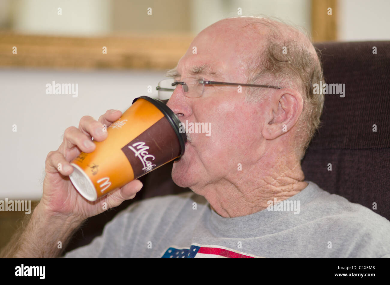 An elderly Causasian man drinks coffee from a McDonald's cup in his own home. USA - Stock Image