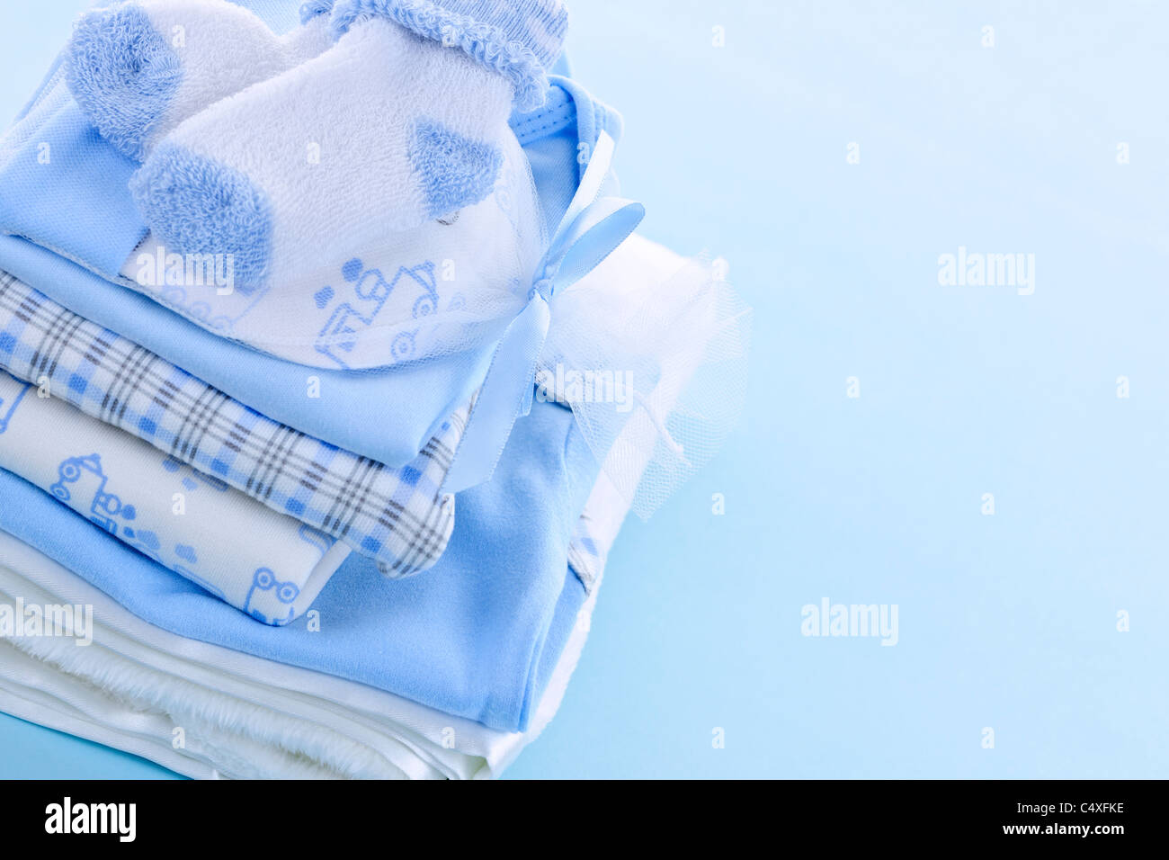 Stack of boy infant clothing for baby shower on blue background ...