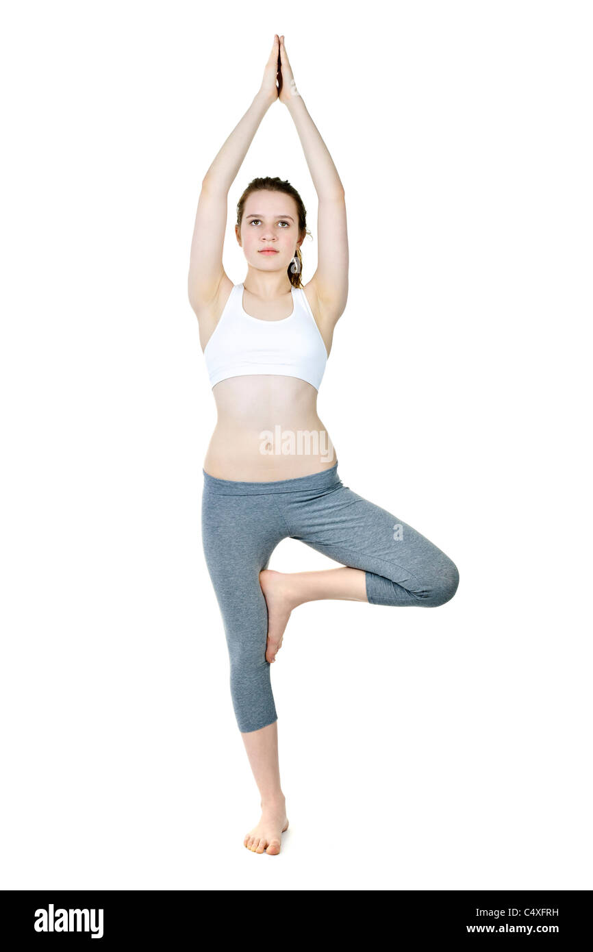 Healthy young woman doing tree yoga pose isolated on white - Stock Image