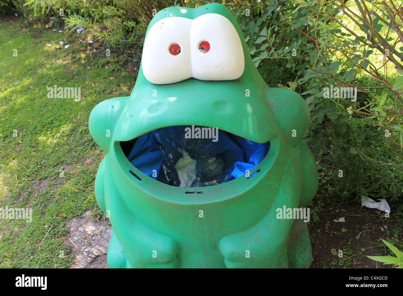 Funny green frog garbage can - Stock Image