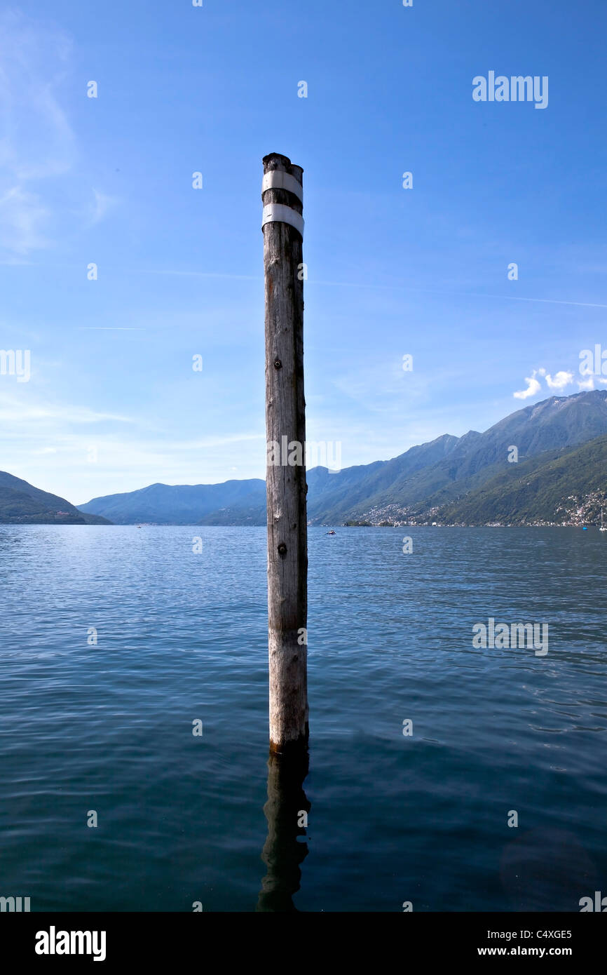 Wooden stake in the Lago Maggiore with views to the south - Stock Image