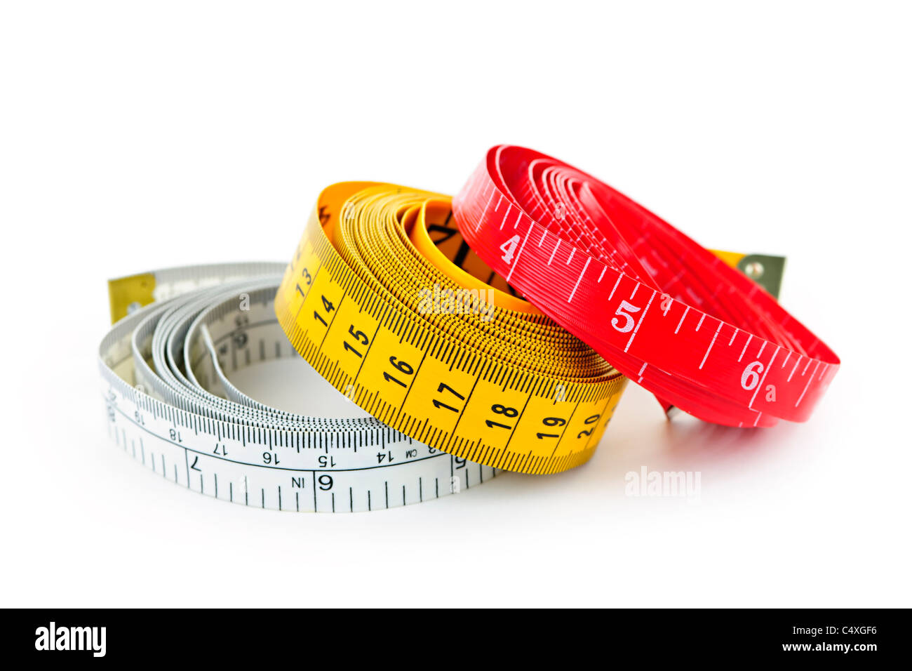 Three colorful measuring tapes coiled on white background - Stock Image