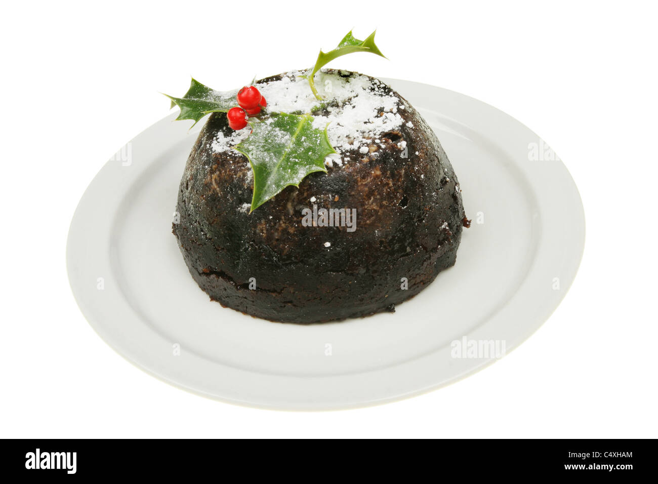 Decorated Christmas pudding on a plate - Stock Image