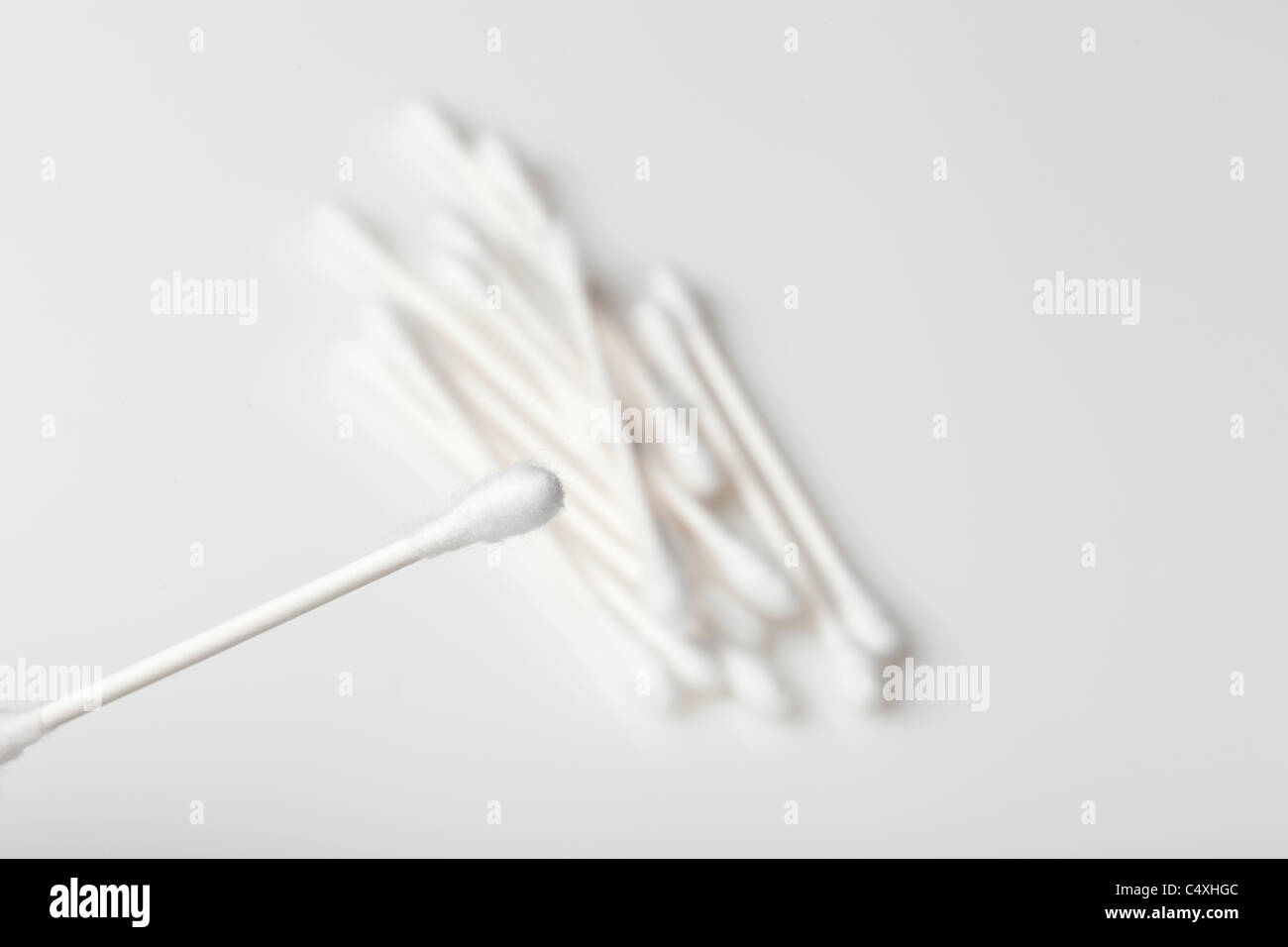 A group of cotton swabs against a white background - Stock Image