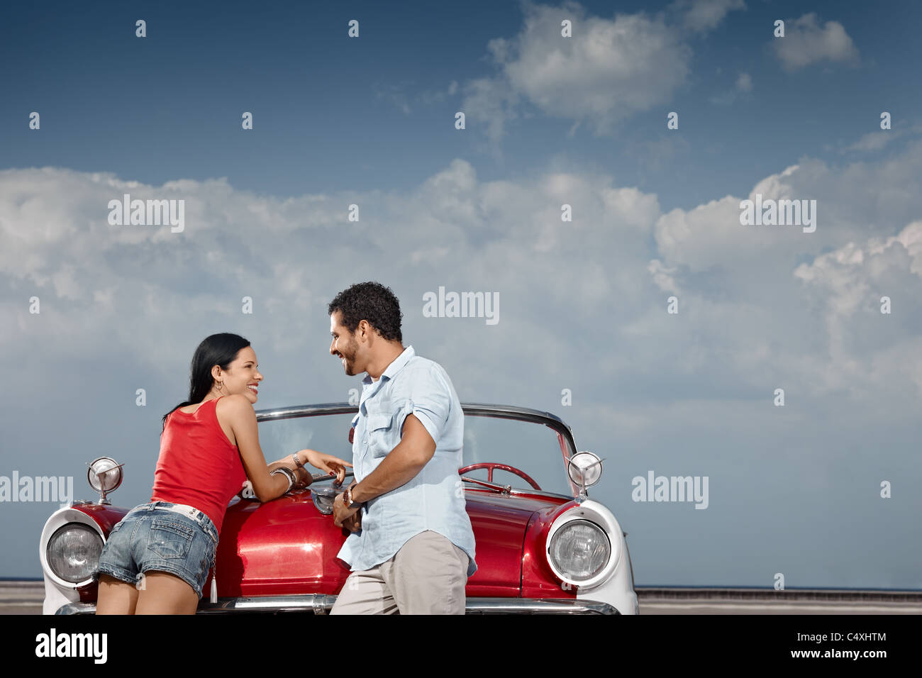 hispanic boyfriend and girlfriend standing near vintage car in havana, cuba. Horizontal shape, side view, copy space - Stock Image