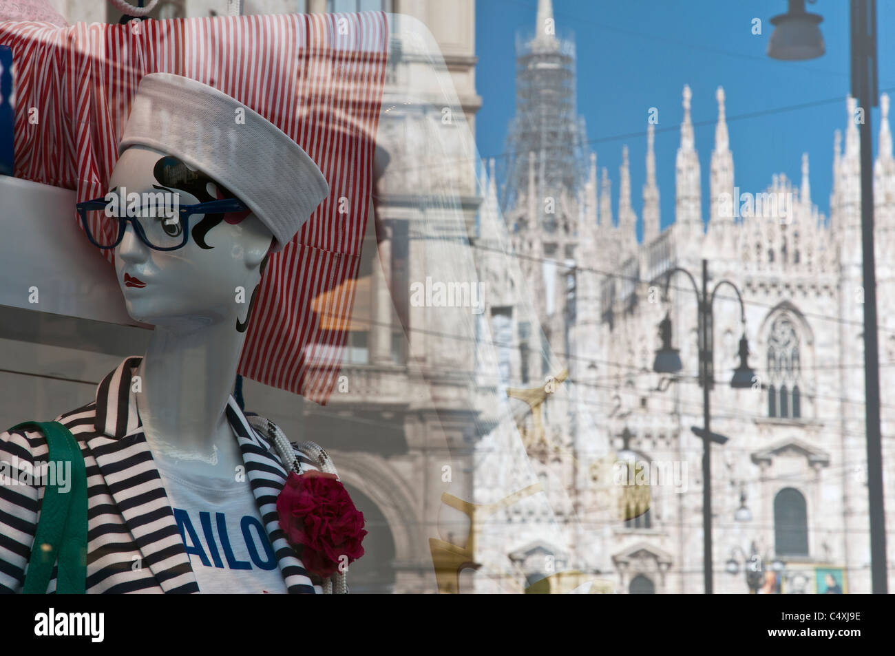 Fashion dummy in a shop window with Duomo cathedral reflected, Milan, Italy - Stock Image