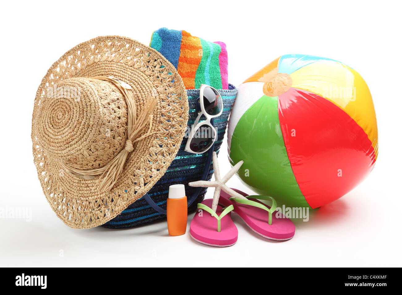 Beach items with straw hat,towel,flip flops,sunblock,beach ball and sunglasses. - Stock Image