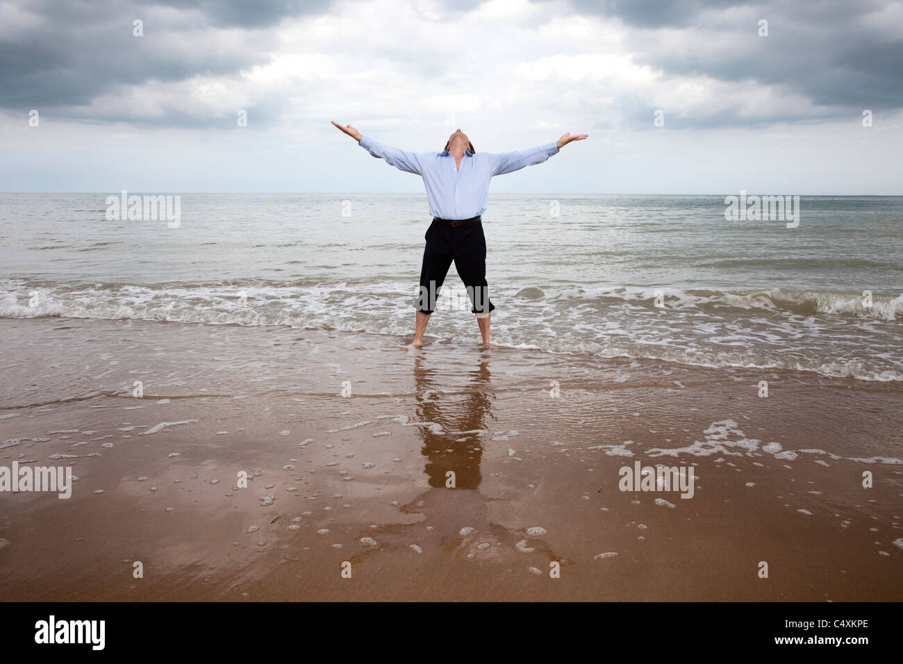 Fully clothed man standing in the sea with arms out looking to the sky. Stock Photo