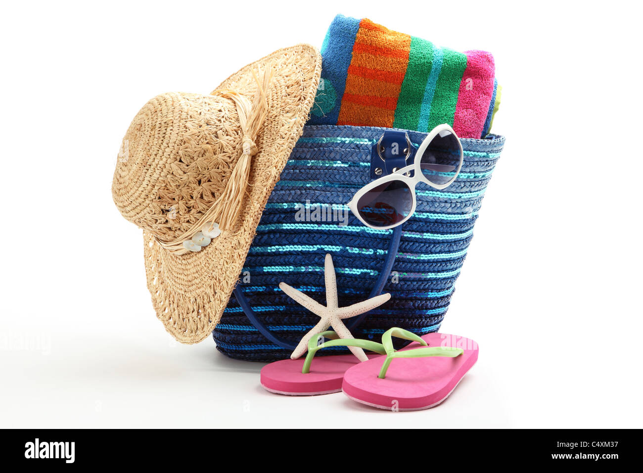 Beach bag with straw hat,towel,flip flops and sunglasses.Isolated on white background. - Stock Image