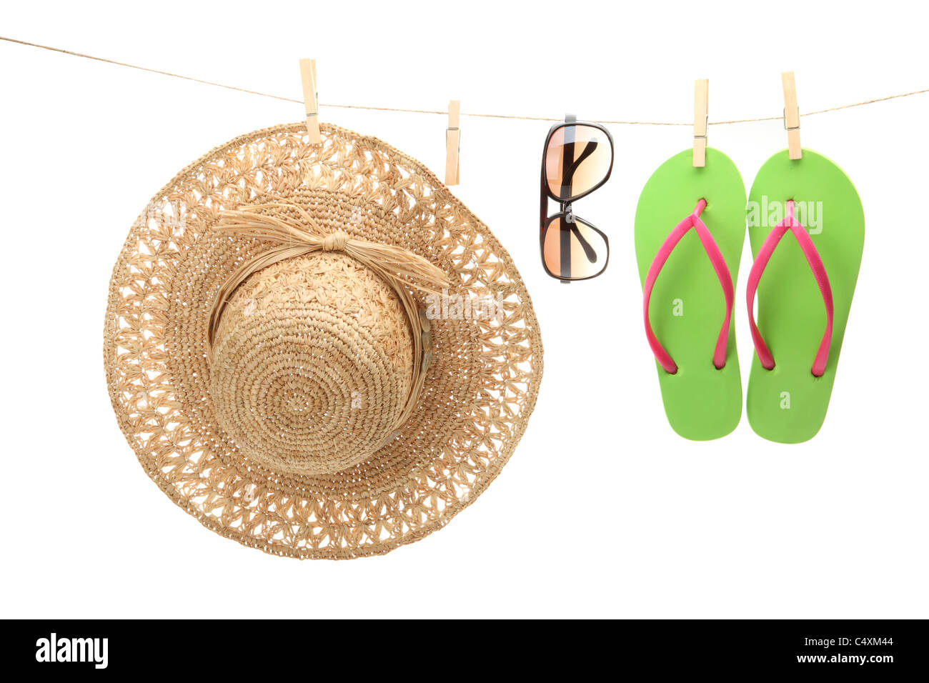 Straw hat,sunglasses and flip flops hanging on clothes line. Stock Photo
