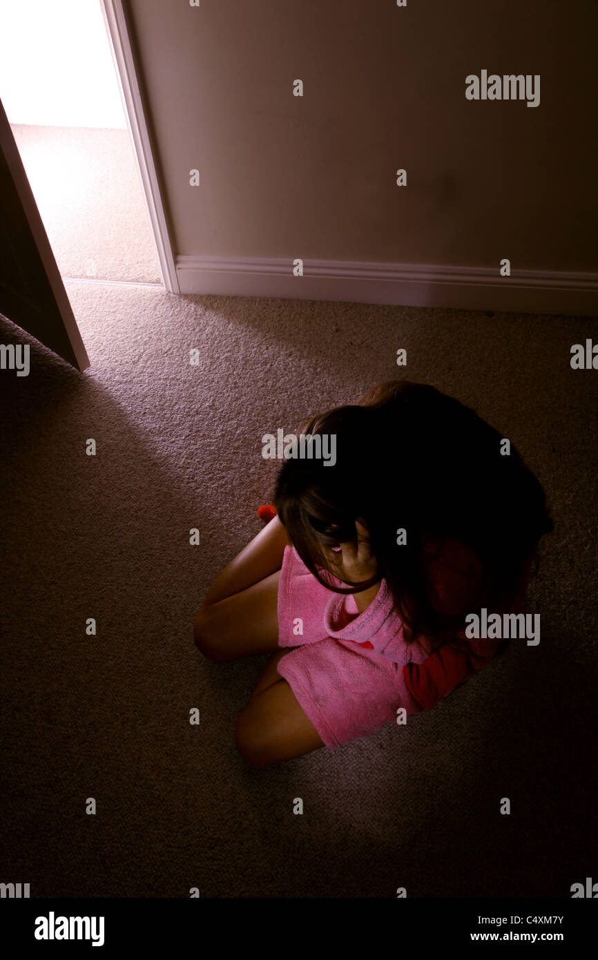 Young female sitting alone in a dark room wearing a pink dressing gown looking down. - Stock Image