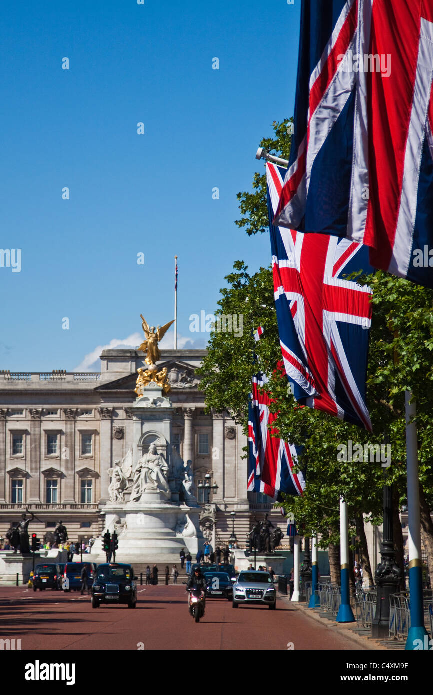 Queen Victoria memorial in front of Buckingham palace with Union flags on the Mall - Stock Image