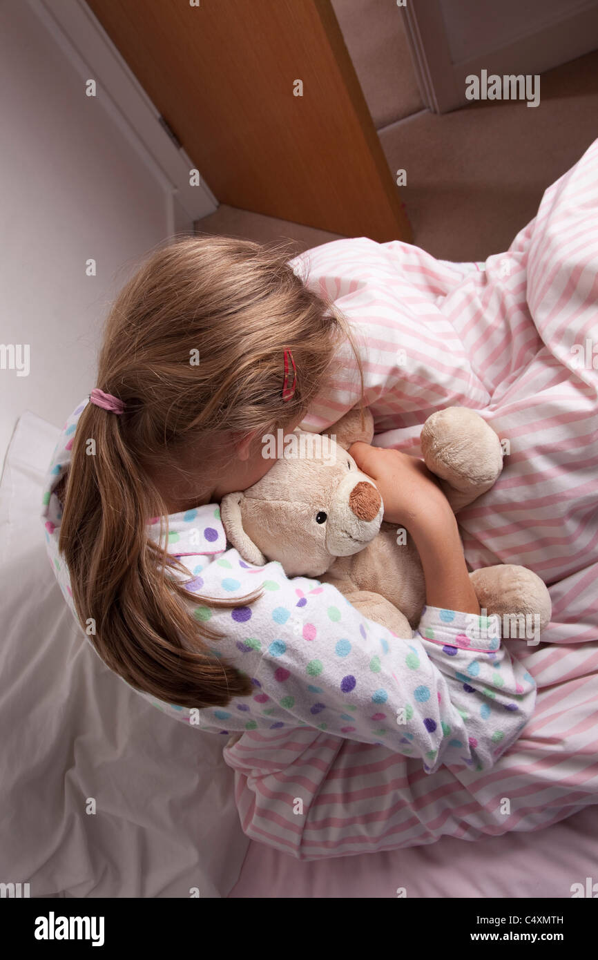 Young girl cuddling a teddy bear sitting on the bed, head down. Stock Photo