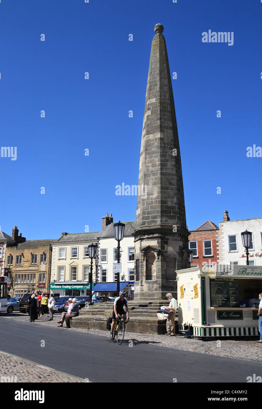 A man cycles past the obelisk in Richmond market place, North Yorkshire, England, UK Stock Photo